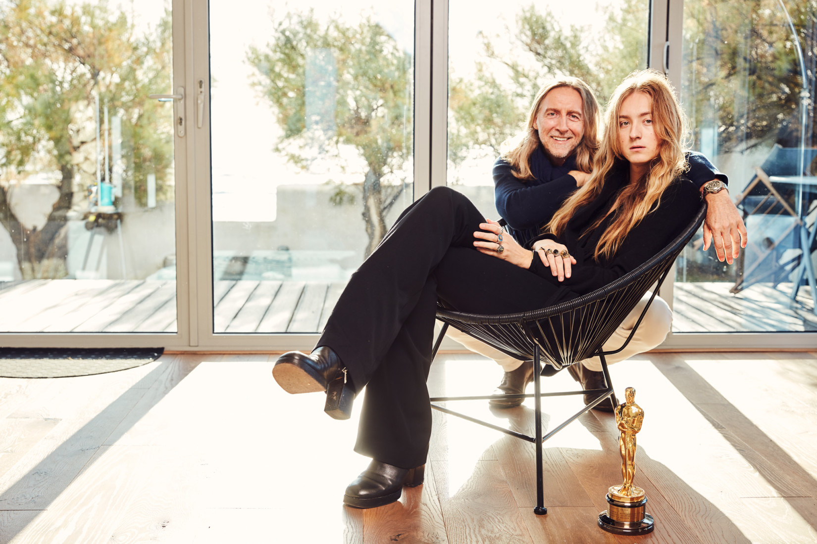Nick and Harris Reed sit on a chair with an Oscar statue